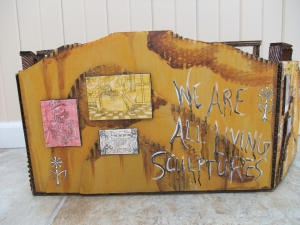 "Back view, depicted as a wall in an abandoned house complete with skeletal themed artwork and wallpaper print, ""We are all living sculptures"""