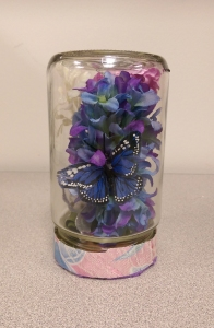 Decorative Terrarium by Michelle : All you need is an empty salsa jar, some fabric flowers on stems, ribbon to wrap around the lid base, and a little bit of creativity.